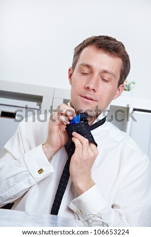 Business man making tie knot in his office - stock photo