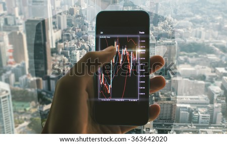 Business man making trading from his office. Close up on the smart phone with trading chart - stock photo