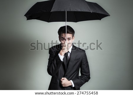 Business man making worried face while holding on tight to and umbrella.  - stock photo