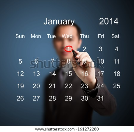 business man marking new year day on January 2014 calendar