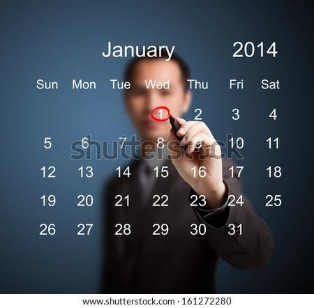 business man marking new year day on January 2014 calendar - stock photo