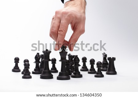 Business man moving chess figure - stock photo