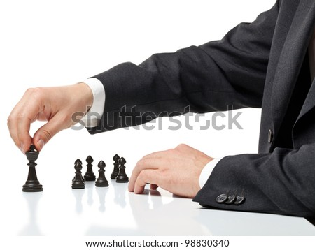 Business man moving chess figure with team behind - strategy or management concept - stock photo