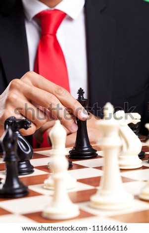 Business man moving his king on the chessboard
