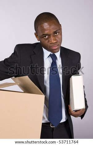 Business man moving out with a cardboard box and a book - stock photo