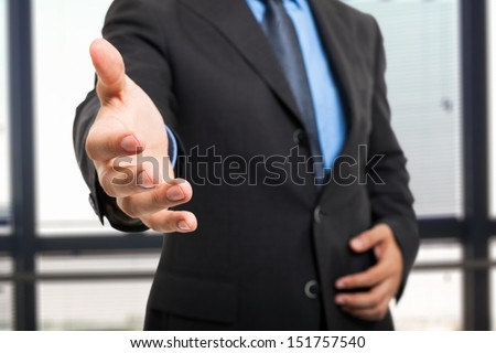 Business man offering an handshake - stock photo