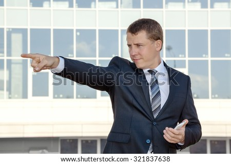 Business man on the background of an office building. He points his finger to the side. Pointing to the side. In his hand phone. - stock photo