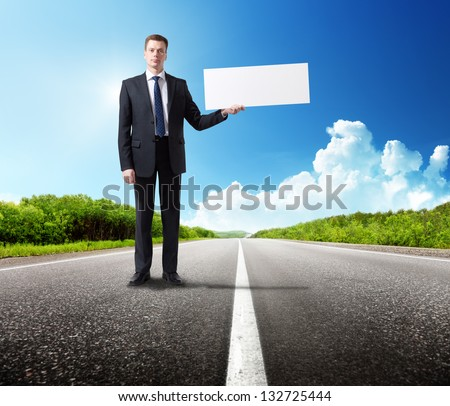 business man on the road with blank in hand - stock photo