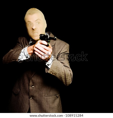Business man or corporate crook holding hand gun with angry expression isolated on black background - stock photo
