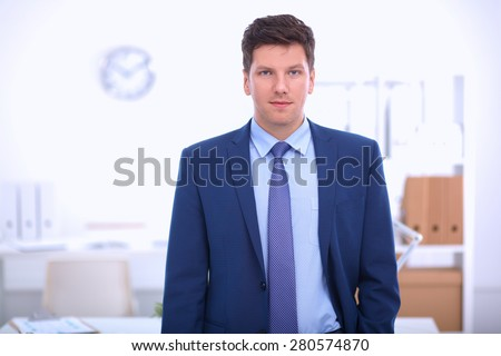 Business man or manager standing against his desk at the office . - stock photo