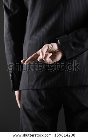 Business man or politician  with fingers crossed behind back  - stock photo