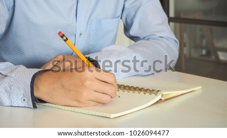 Business man or university student hand holding pen writing new project or ideas on diary notebook page