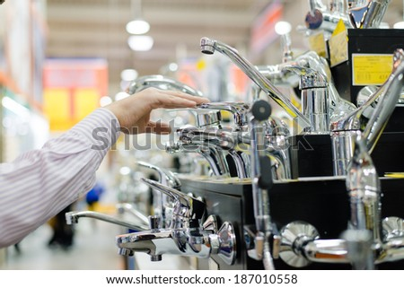 business man or woman choosing and touching faucet crane or water tap on shopping shelf display of DIY department - stock photo