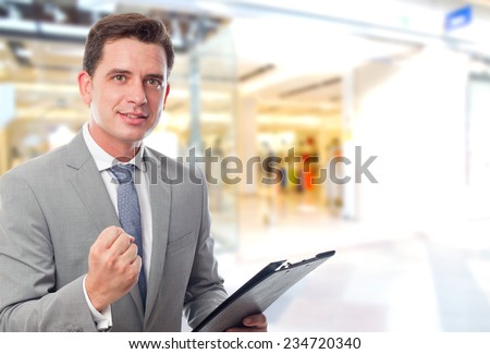 Business man over shopping center background. Looking happy - stock photo
