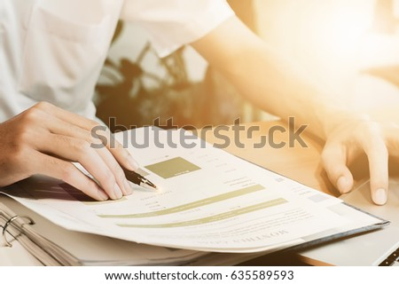 Business man pen  pointing stock market document and use laptop with  doing finance at home office.