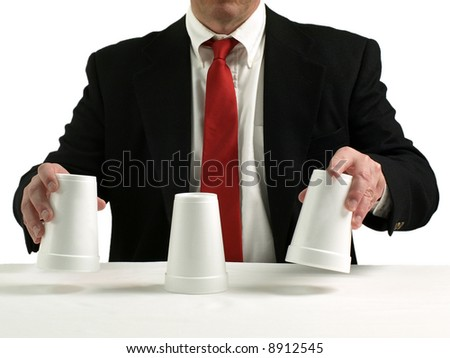 business man performing shell game scam with cups - stock photo
