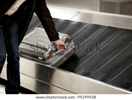 Business man picking up metal suitcase from conveyor belt at airport - stock photo