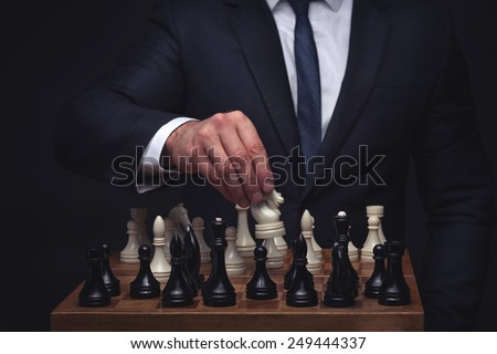 business man playing chess on dark studio background
