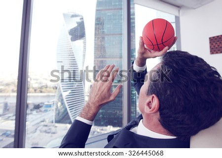 Business man playing with a basketball at the office - stock photo
