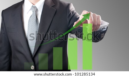 Business man pointing at green bar chart for business growth concept - stock photo