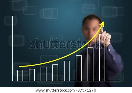business man pointing at upward trend graph - stock photo