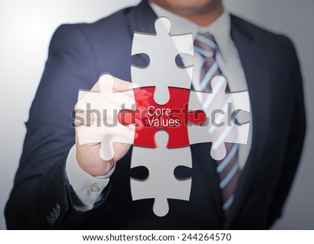 Business Man pointing on jigsaw written Core Values - stock photo