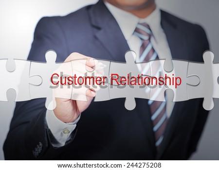 Business Man pointing on jigsaw written Customer Relationship - stock photo
