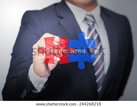 Business Man pointing on jigsaw written Customer service - stock photo