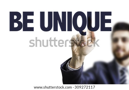 Business man pointing the text: Be Unique