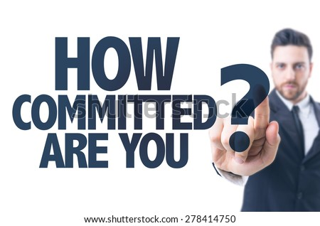 Business man pointing the text: How Committed Are You? - stock photo