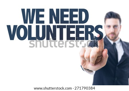 Business man pointing the text: We Need Volunteers - stock photo