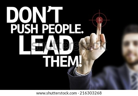 Business man pointing to black board with text: Don't Push People, Lead Them! - stock photo