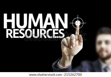 Business man pointing to black board with text: Human Resources - stock photo