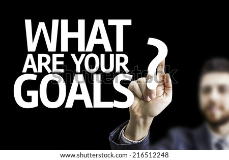 Business man pointing to black board with text: What are Your Goals? - stock photo