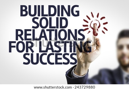Business man pointing to transparent board with text: Building Solid Relations For Lasting Success - stock photo