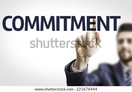 Business man pointing to transparent board with text: Commitment - stock photo