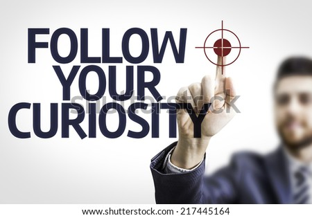Business man pointing to transparent board with text: Follow your Curiosity - stock photo