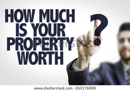 Business man pointing to transparent board with text: How Much is your Property Worth? - stock photo