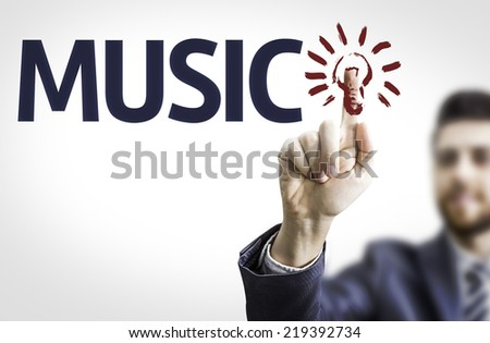 Business man pointing to transparent board with text: Music - stock photo
