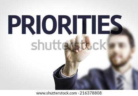 Business man pointing to transparent board with text: Priorities - stock photo