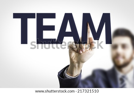 Business man pointing to transparent board with text: Team - stock photo