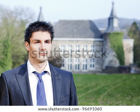 Business man portrait  in front of his castle - stock photo
