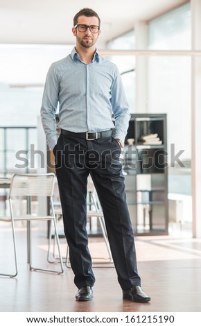 Business man posing in an office environment - stock photo