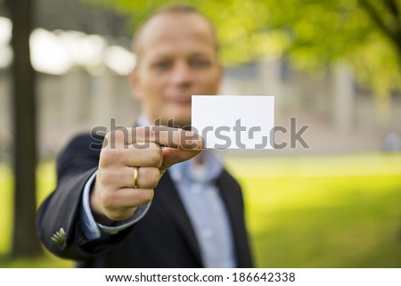 Business man presenting a business card, standing outdoors on the grass in front of a convention center. Focus on the hand and business card - stock photo