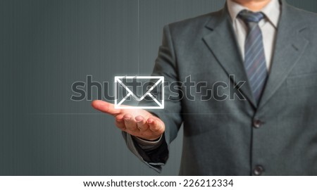 Business man Presenting Email Icon Over Grey Background