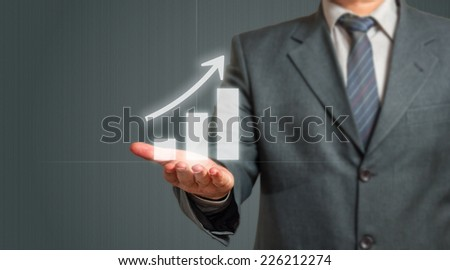 Business Man Presenting  Growing Graph Over Grey Background