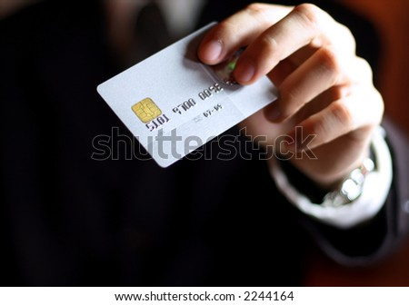 Business man presenting his credit card. Shallow DOF, focus on chip o card. Concept: Shopping and spending. - stock photo