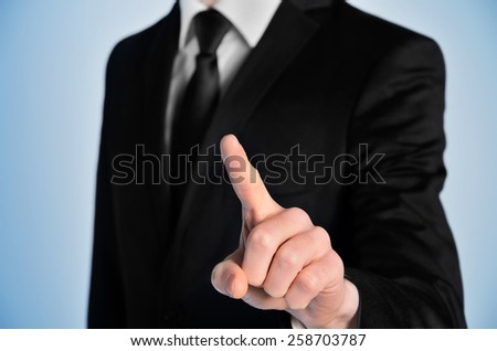 Business man press something on blue background