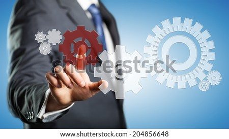 business man pressing a specific cog wheel to keep the system running - stock photo
