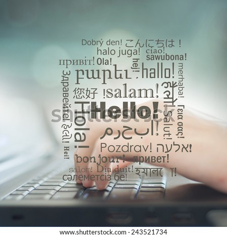 Business man pressing buttons on laptop, on the screen Hello in different languages - stock photo